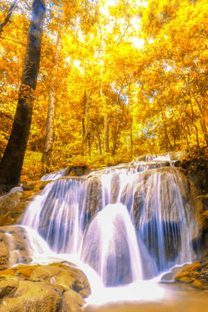 Landscape autumn waterfall in a colourful forest, bright colours leaves in seasonal. Long exposure. Фото со стока