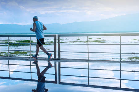 Motion blur. An Asian senior man in fitness wear running in a park along a lake at sunrise, blue mountains blurred in the background.