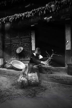 A Chinese old man making corn chair at his yard, corn cob hanging on wooden lintel of ancient house. Chengzi Village, Yunnan, China. Focus on old man.