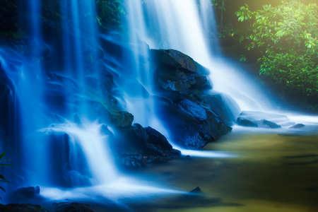 Pure tropical waterfall at sunrise, fresh green foliage grownig near a waterfall in rain season. Thailand. Long exposure.
