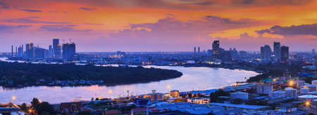 Panoramic aerial view of Bangkok skyline and Chao Phraya river at twilight, illuminated lights of business district and port. Thailand. Focus on port in the foreground.