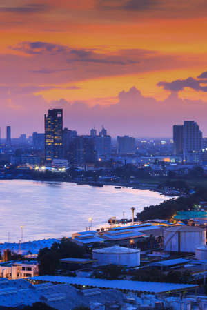 Aerial view of Bangkok skyline and Chao Phraya river at twilight, illuminated lights of business district and port. Thailand. Focus on port. Фото со стока