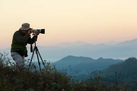 Side view of a senior man taking pictures with camera and telephoto zoom lens on tripod on the mountain peak at sunrise.