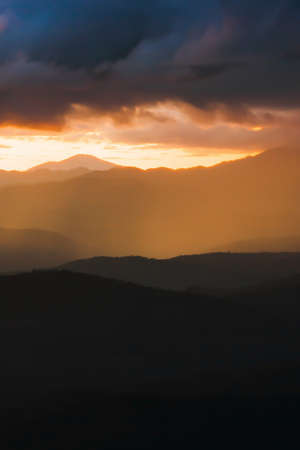 Scenery mountain range at sunset, dramatic rainstorm hiding the setting sun in the background, magical spotlight shines through dark clouds onto mountains. Focus on mountains.