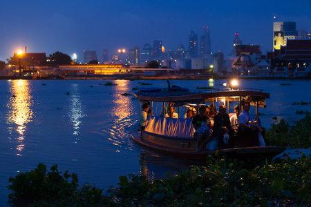 Bangkok, Thailand - September 12, 2013: Thai people on a wooden ferry boat on Chao Phraya River at dusk. Bangkok. Editorial