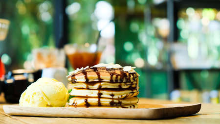 Sweet banana pancakes stack with macadamia nut and chocolate syrup topping on pancake flat lay on wooden plate, green garden blurred in the background. Close-up. Soft focus on pancakes. Imagens