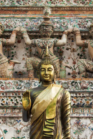 Golden Buddha figures in front of ancient pagoda, giant guardian statues with ceramic mosaic tiles decorated blurred in the background. Wat Arun (Temple of Dawn), famous place in Bangkok, Thailand. Imagens