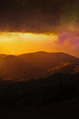 Dramatic rainstorm hiding the setting sun and mountain ridge, magical spotlight shines through dark clouds onto the mountains. Focus on mountains.