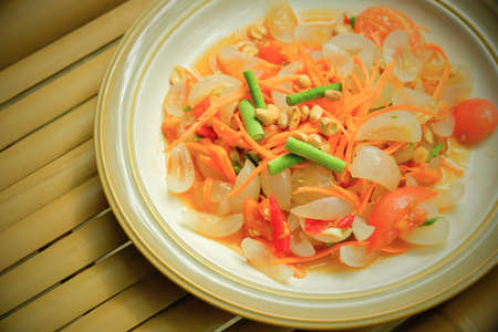 Green papaya salad, spicy Thai fruit salad with nipa palm fruit or mangrove palm fruit on white plate flat lay on the table. Close-up. Top view. Selective focus.