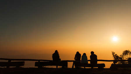 A group of tourists sits on the logs at viewpoint while  relaxing on a mountain peak at sunrise, the rising sun over a mountains in the backgrounds. Holiday, Vacations concepts.