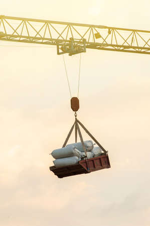 An old hammerhead crane lifting tray of cement bags at a construction site, sky in the background.