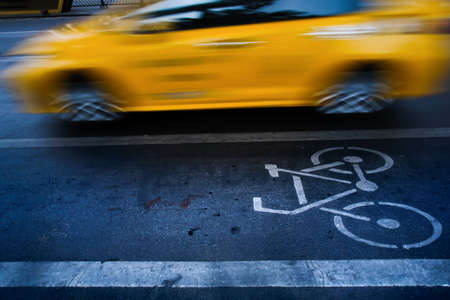 Separate bicycle lane and bike path sign on an asphalt road, traffic speed past. Top view. Motion blurred. Imagens