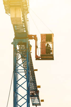 An Asian man crane operator climbs the crane ladder of the old hammerhead crane to the control cabin at a construction site. Focus on the crane. Imagens