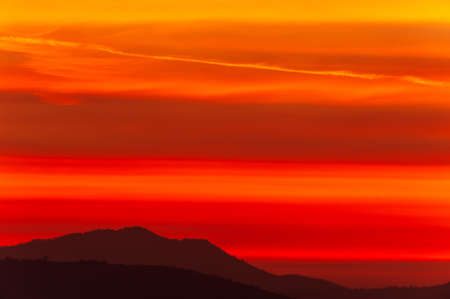 Dramatic clouds on the sunset sky over mountains, magical ripples clouds on the red sky. Focus on the sky.