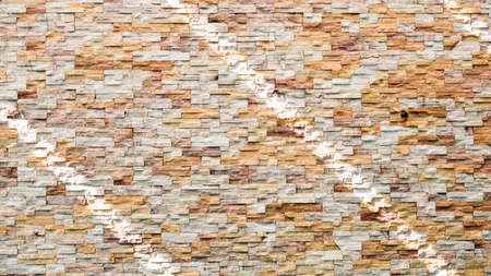 Abstract brown and white rock stone wall texture. Striped shadow and light on stone wall or stonework background. Home, Residential building. Imagens