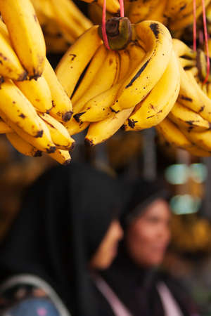 Close-up ripe bananas fruits display at a local grocery. Bunch of ripe yellow bananas fruits with dark spots display at a local grocery. Females vendor blurred in the background. Imagens