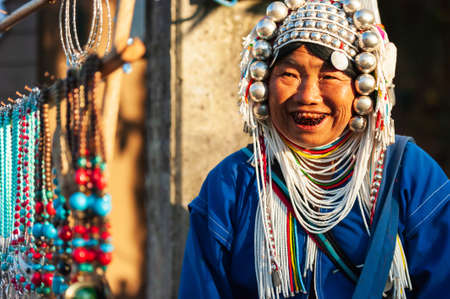 Chiang Rai, Thailand - December 3, 2014: An elder Akha woman in traditional clothing selling Akha traditional souvenir handmade, accessories, necklace, silver and bead at local market. Doi Mae Salong.
