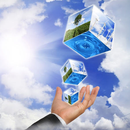 transformation: Business man hand holding with nature water drop and wind  turbines farm on sky
