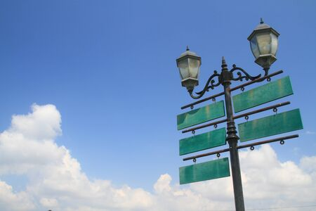 a signboard: Antique lamp with traffic wood signboard on sky Stock Photo