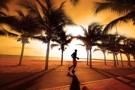 keep fit: Sillouette of the man jogging  The coconut trees on the beach at sunset  Stock Photo