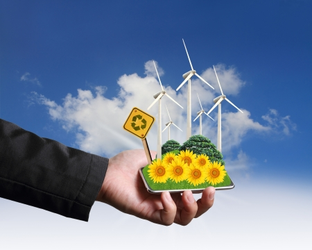 Business man hand holding with wind turbines farm eco concept photo