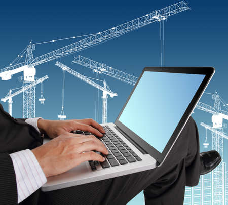browsing: Businessman hands typing on laptop keyboard with crane illustration background