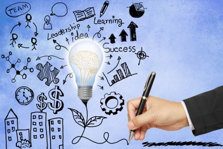 lluvia de ideas: Negocios dibujo a mano bombilla con la ilustraci�n de los s�mbolos en el fondo de papel azul Foto de archivo