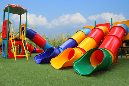 yellow: colorful playground park is build happy equipment children on blue sky, flower and grass Stock Photo