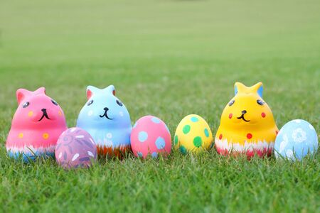Colorful ceramic rabbit with eggs on top grass on Easter Stock Photo