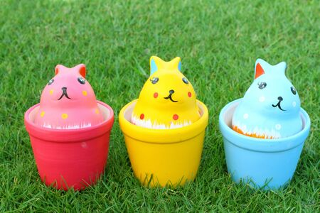 Colorful rabbits in ceramic cups on grass background Stock Photo