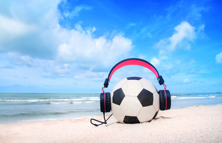 escuchar: pink headphones,football on blue sky and beach background. Foto de archivo