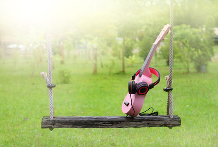 sweet pink headphones, ukulele music on wooden swing and green grass background