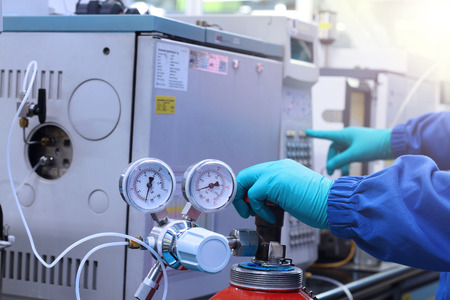 chromatograph: hand work and start Gas Chromatography Analyzer in laboratory. Stock Photo