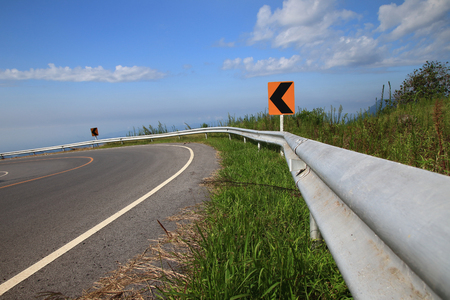 Curve road sign on down hill blue sky background 写真素材