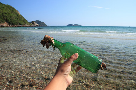 Green glass garbage Collected from the sea on beach background. There are clams, barnacles