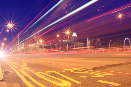 Luces de velocidad rojas de autobuses y automóviles en una carretera a la ciudad