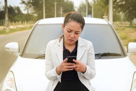 Woman business searching for phone contacts for help from the broken car Imagens
