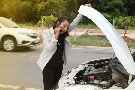 Woman business calling phone fore help from the broken car. Woman business at broken car on road and calling on cellphone for help.