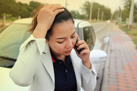 Woman business calling phone for help from the broken car. Woman business at broken car on road and calling on cellphone for help.