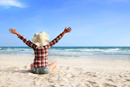 A woman wearing a plaid shirt raises her hands showing a refreshing on sky at a beautiful beach Imagens