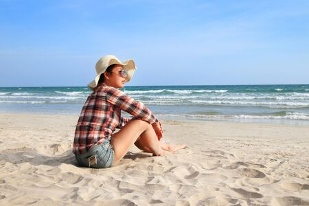 Asian woman wearing a plaid shirt at relax time on a beautiful beach Imagens