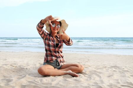 Healthy woman smile and take a hands framing distance on seaside nature background Imagens