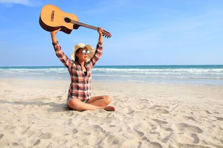 A woman wearing a plaid shirt and lifting the guitar on a beautiful beach. Asian beautiful girl wearing plaid shirt playing guitar on a beautiful beach