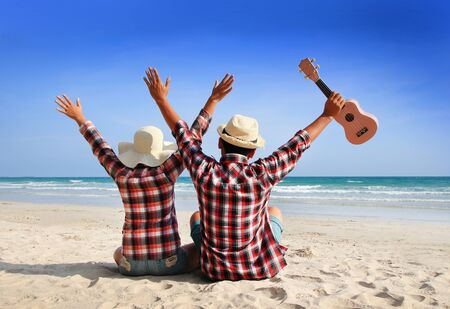 Couples are holding hands to soak up the seaside nature. Man and woman wearing a plaid shirt raises both hands showing a refreshing on sky at a beautiful beach Imagens