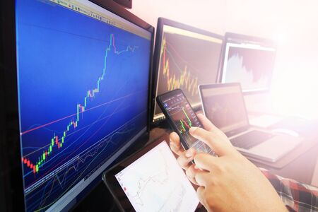 Business hands are using smartphone for investment in stocks investment concept Imagens