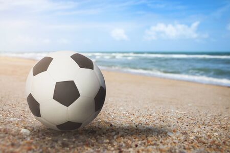 Soccer ball object are placed on beach and bright sky.Summer holiday on the beach concept. Imagens