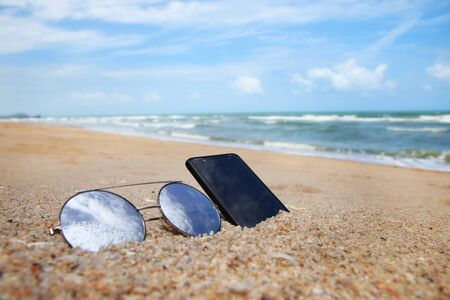 Sunglasses and phone are placed on beach and reflections of bright sky.Summer holiday on the beach concept.
