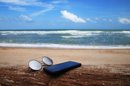 Sunglasses and phone are placed on dry logs and reflections of bright sky. Summer holiday on the beach concept.