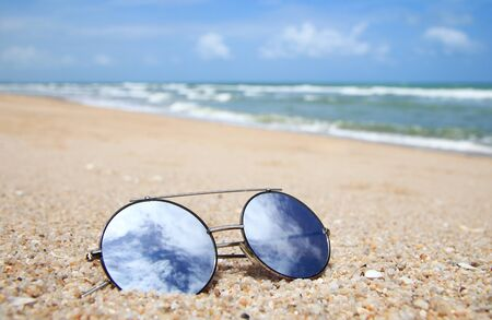Sunglasses are placed on the beach with the reflection of the bright sky. Summer holiday on the beach concept.