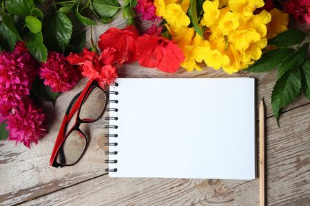 Colorful florals white notebook placed on the table old wooden background